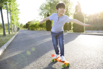 Happy little boy skateboarding