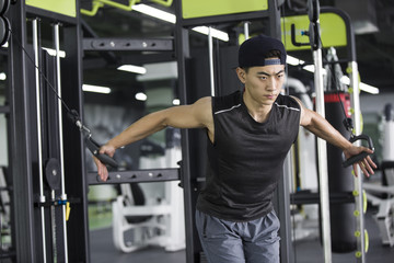 Young man using exercise machine at gym