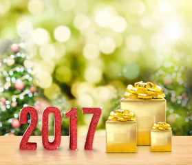 2017 red glitter and Golden present on wood table with christmas