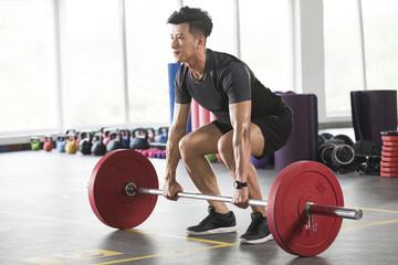 Young man lifting barbell at gym