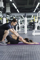 Young woman working with trainer at gym