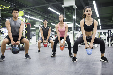 Young adult working with trainer at gym