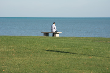 Guy sitting on a bench on a lake