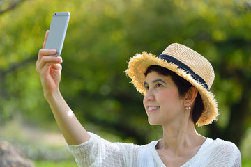 Happy middle aged woman smiling a perfect smile and white teeth taking a selfie on her phone in the park              ..