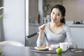 Young woman eating breakfast at home