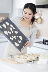 Young woman making cookies in kitchen