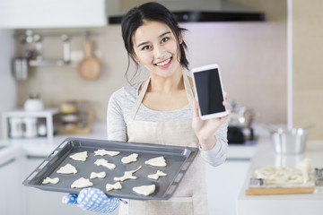 Young woman baking cookies in kitchen