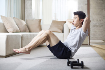 Young man exercising at home
