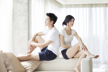 Angry couple sitting on living room sofa