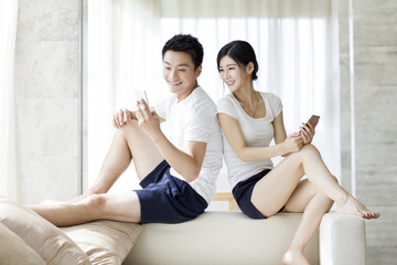 Happy young couple using smart phone at home