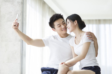 Happy young couple taking self portrait with a smart phone