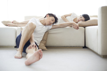 Young couple sleeping in living room