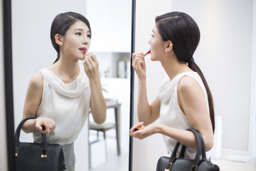 Young woman looking into a mirror applying lipstick