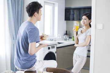 Happy young couple having breakfast at home
