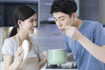 Happy young couple cooking in kitchen