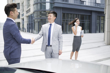 Confident business people shaking hands outdoors