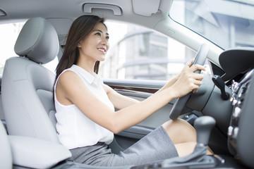 Confident businesswoman driving car