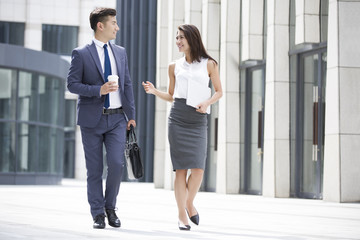 Confident business people talking and walking outdoors