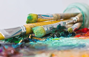 artist's palette with oil paints and brushes used for painting a