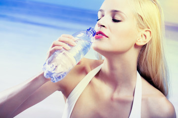 Portrait of young woman drinking water on beach
