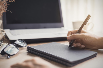 woman writing on notebook at workplace