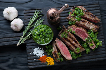Medium rare grilled, sliced rumpsteak with chimichurri sauce
