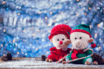 Happy Christmas Elf Family With Candy Canes On Snowy Wooden Background.