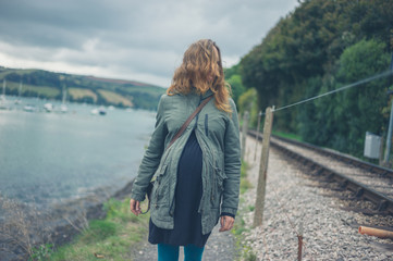 Pregnant woman walking by river and railroad tracks