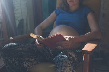 Pregnant woman reading by window