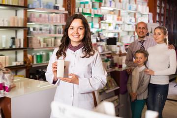 Woman pharmacist helping customers