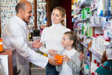 Mature male pharmacist helping customers