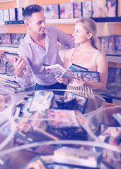 Couple choosing disks with video in sex shop.