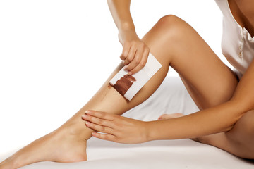 woman waxing her legs using tape and wax for depilation
