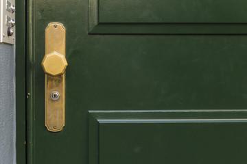 A dark green painted wooden door with golden octagonal knob and door bells on the left side