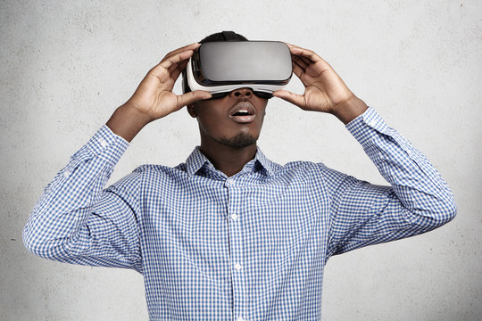 People, technology, innovation and gaming concept. Astonished African businessman in checkered shirt experiencing virtual reality while using oculus rift headset for entertaining himself in office