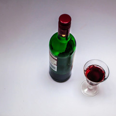 A bottle of red wine with glass