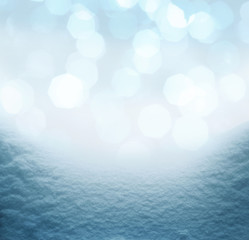 Winter background with pile of snow and blur abstract lights.