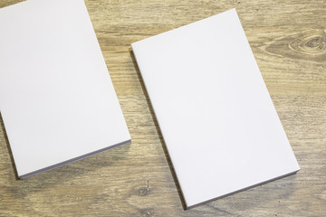 Real 3D paperback white books on a wood background