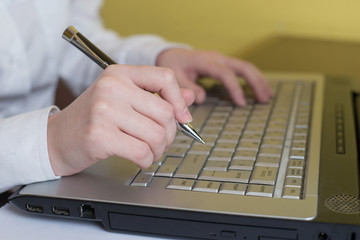 Woman hands typing on laptop keyboard. Holding pen in arm. Selective focus on hand. Can be used for technology, business and internet concept.