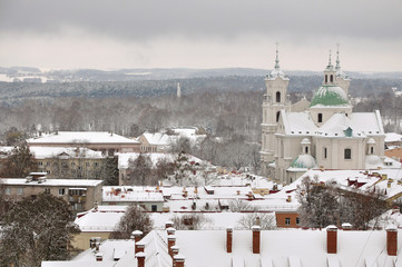 Panorama Grodno after a snowfall. Roofs of old houses and a Catholic church in the Baroque style covered with snow in perspective. Belarus winter.