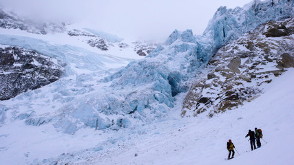 a mountain guide and clients below a glacier in the Swiss Alps on a backcountry ski excursion