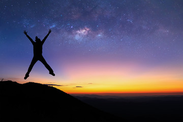 Silhouette of woman is jumping on top of mountain and enjoy to see the milky way before sunrise.