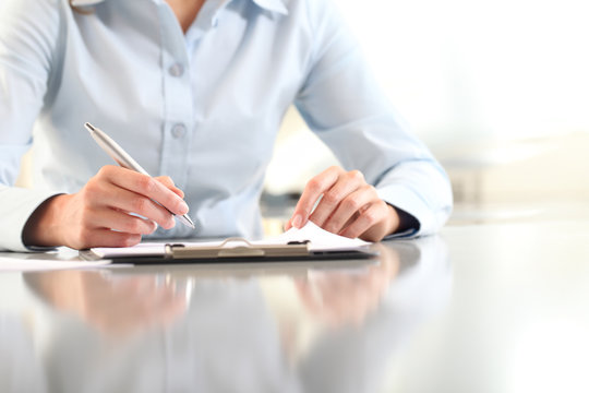 woman hands writing on clipboard with a pen, isolated on desk