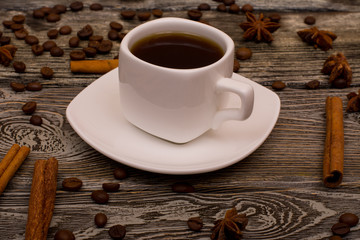 Small white cup of coffee, cinnamon sticks, cocoa beans, star anise on wooden background
