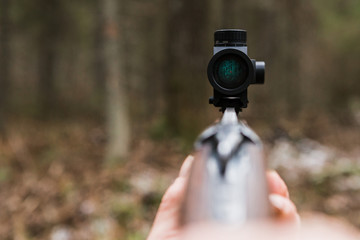 Hunting rifle sight, close-up. Optical sight. A red dot. A man holding a gun.