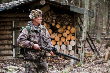 Man the hunter is in the forest in rubber boots, with a backpack and a gun. Cloudy weather, autumn. Against the background is seen the wooden lodge. Around the house are wood for the fire.