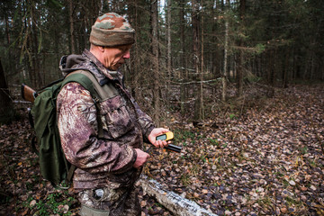 Man hunter with a gps navigator in the forest. Orienteering in the forest, a route map. Technology, Gadget.