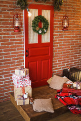 Christmas decor. Festively decorated Christmas interior in red and brown colors. Vertical color image of photo booth with brick brown wall, painted door, wrapped presents, pillows, hanging lanterns.