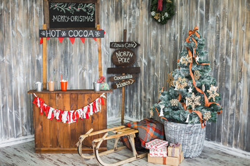 Beautiful colorful festively decorated interior for Christmas holiday celebration. Photobooth with wooden walls. winter sleigh, blanket, Christmas tree in painted basket. wrapped gift boxes.