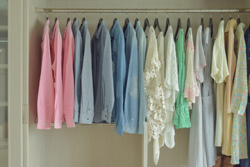 Women cloths hanging in wooden wardrobe